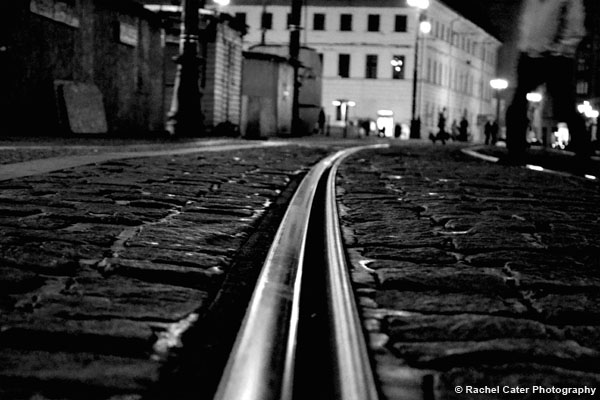 Man walking across tracks in Prague BW Rachel Cater Photography